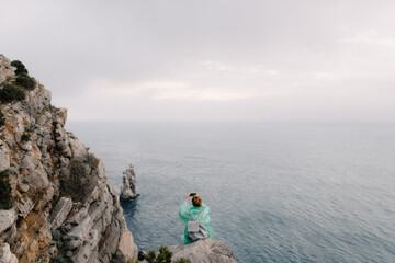 Female sitting on the edge of cliff among the ocean and taking pictures on her smartphone
