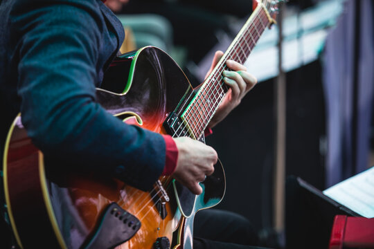 Concert view of an electric acoustic guitar player with vocalist and musical jazz band orchestra performing in the background, guitarist on the stage
