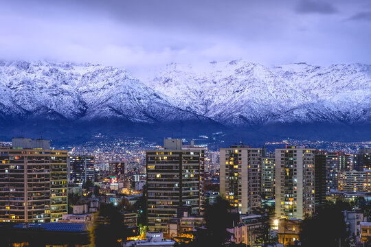 Panorama of amazing purple cloudy sky over Santiago skyline and the snowed Los Andes mountains at the nightfall, Chile