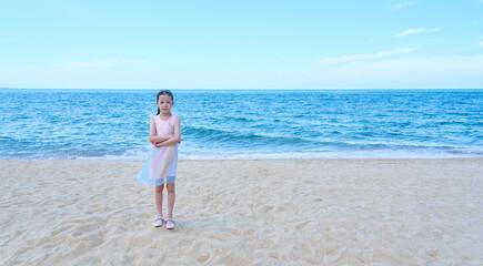 Lovely asian little girl in a pink shirt on tropical beach