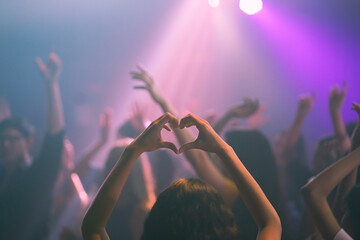 group of young girl dancing in the nightclub, young lady with shape heart in event concert