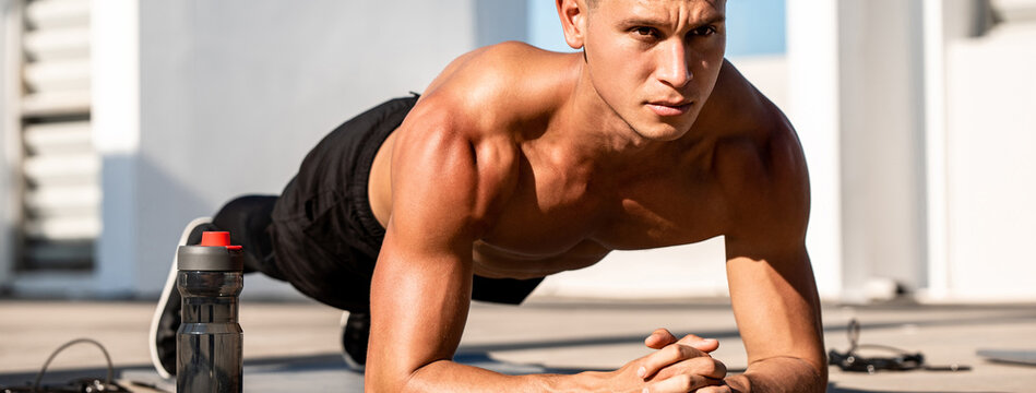 Banner image of handsome muscular sports man doing plank exercise outdoors on rooftop