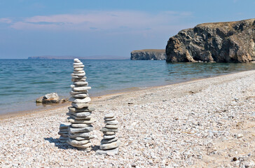 Baikal Lake at sunny summer day. Beautiful beach with tourists stone pyramids on the shore of Olkhon Island. Natural background. Holidays by the lake and travel around the island