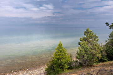 Baikal Lake. Shore Olkhon Island on a foggy summer morning. Beautiful lake landscape with green larch trees near the pebble beach. Summer travel. Natural background