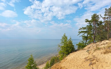 Baikal Lake. Sandy hills with coastal larch forest on the shore of Olkhon Island. Beautiful lake landscape. Summer travel. Natural background