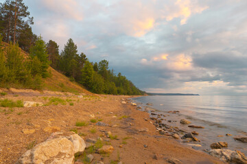 Baikal Lake at summer calm evening. View on the sandy  beach of Olkhon Island at sunset. Beautiful landscape with colorful clouds over water of Small Sea Strait. Natural background. Summer travel
