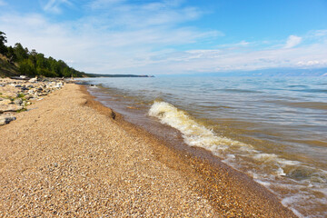 Baikal Lake on a summer day. Pebble wild beach on Olkhon island in Sasa area. Beautiful landscape of the coast of the Small Sea Ыекфше. Summer travel. Natural background