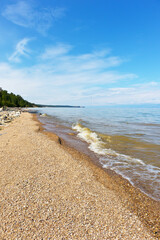Baikal Lake. Beautiful summer landscape of the Small Sea Strait coast with a pebbly beach of Olkhon Islands in the Sasa area. Summer travel. Natural background