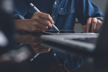 Male graphic designer using stylus pen working on digital tablet on office