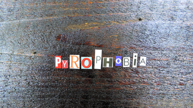 Pyrophobia word from paper letters on wooden boards, fear of fire and sparks