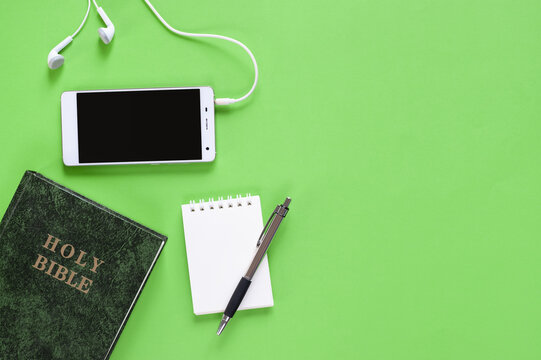 Top view of Holy Bible, phone, and mini notebook on green background
