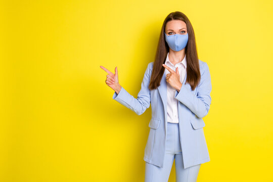 Photo of boss executive business lady point index finger copyspace present covid ads promotion wear blue jacket blazer pants trousers medical mask isolated bright shine color background