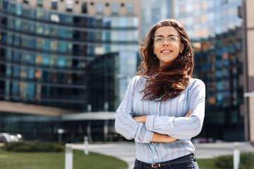 Portrait of confident smiling young businesswoman with glasses standing in city center with crossed arms