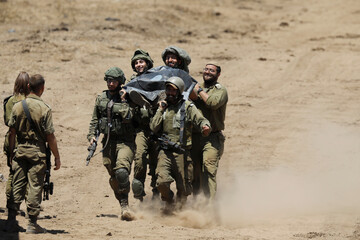 Israeli soldiers carry a stretcher as they take part in a drill in the Israeli-controlled Golan Heights near the Israel-Syria frontier