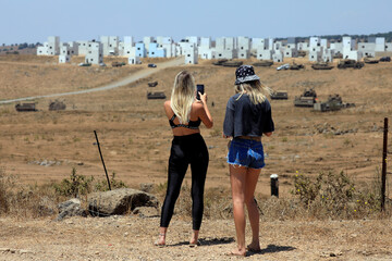 Israeli women look on and use their mobile phone outside an urban warfare training base during a drill in the Israeli-controlled Golan Heights near the Israel-Syria frontier