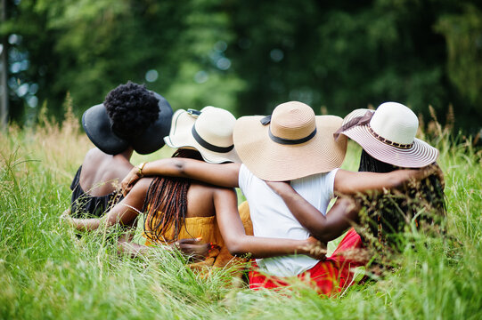 Back view  of group four gorgeous african american womans wear summer hat sitting at green grass in park.