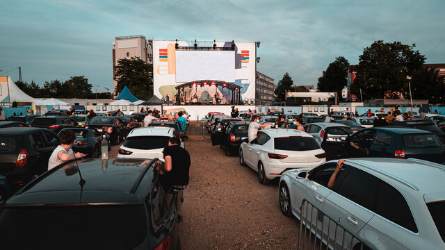 Live show concert in a parking with a lot of cars parked in front of a big scenery to hear music and watch the spectacle inside the car. Concert live show drive-in, open air concert. Social distance