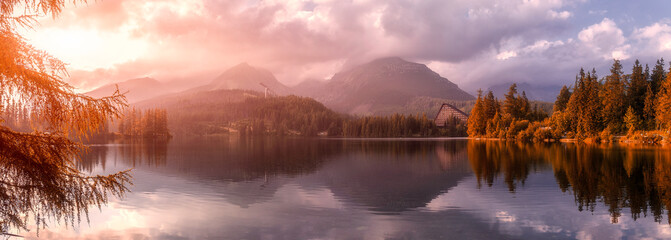 Beautiful sunny landscape. View on mountain lake with crystal clear azure water in High Tatras. Slovakia. Red Boats on the water glowing in sunlight at sunset. Awesome Autumn landscape. Strbske pleso