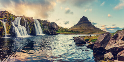 Amazing mountain landscape with colorful vivid sunset on the cloudy sky over the famous Kirkjufellsfoss Waterfall and Kirkjufell mountain. Iceland. popular location for landscape photographers.