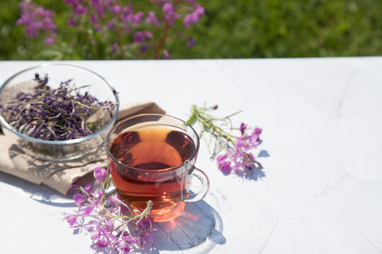 Chamaenerion angustifolium tea (cypress, big willow, pink willow) with dry and fresh flowers for decoration in glass cups on a light background. Concept of herbal medicine. Horizontal orientation