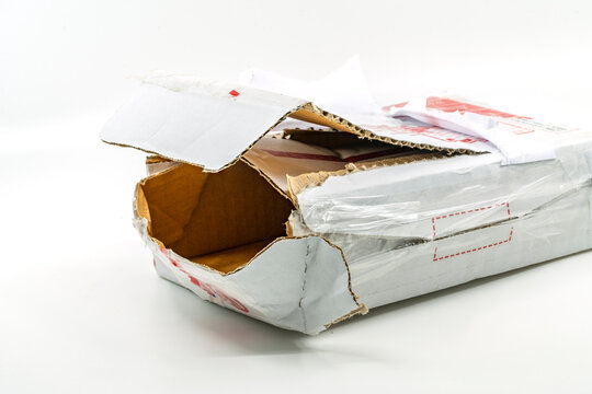 Torn white parcel box on white background. Close up large hole on the parcel box. The stolen internal package box.