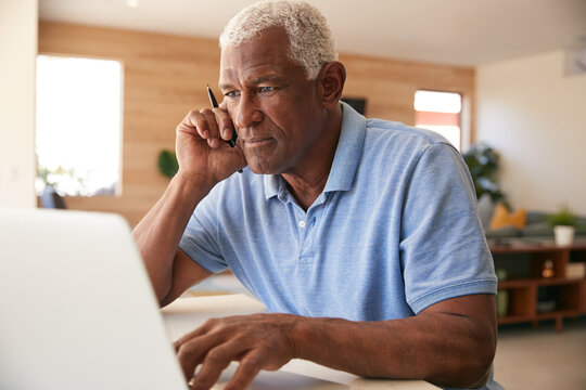 Senior African American Man Using Laptop To Check Finances At Home