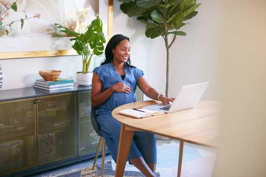 Pregnant African American Woman Using Laptop At Table Working From Home
