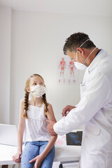 Doctor with mouth mask gives girl with mouth mask an injection against flu or corona