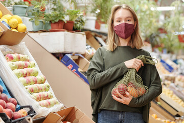 Portrait of pretty girl in mask holding net bag of organic products at farmers market during coronavirus