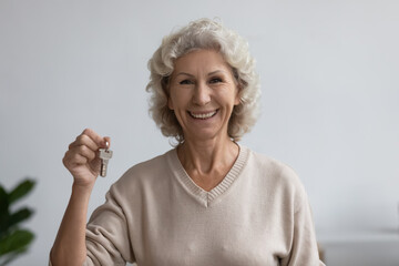 Happy old woman holds bunch of keys standing indoors smile look at camera. New house buying...