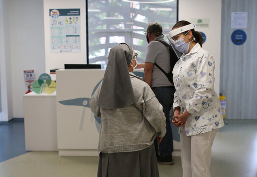 A doctor wearing protective equipment talks to a patient at the reception of the Zerenia clinic, the first clinic specializing in medical marijuana treatments, in Bogota
