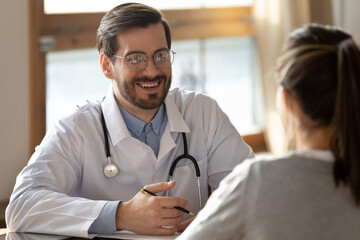 Happy young male family therapist or general practitioner in glasses and medical white coat holding stethoscope on neck, listening to new female patient client at checkup meeting in hospital.