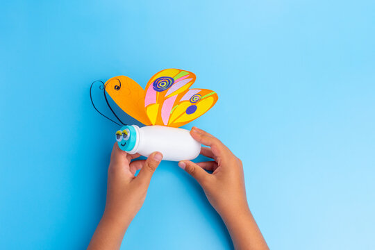 simple butterfly craft from paper and recycled yogurt bottle, DIY . Kindergarten or school, creative craft project ideas, blue background, kids hands hold craft, top view