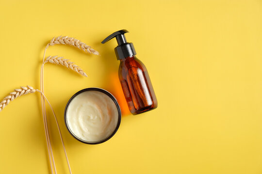Dark amber glass pump cosmetic bottle, moisturizer cream in jar, wheat on yellow background. SPA natural organic beauty products, skin care concept.