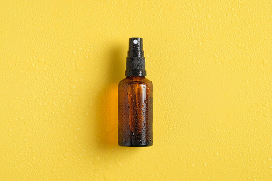 Wet amber glass spray bottle mockup with water drops on yellow background, view from above. Suntan lotion.
