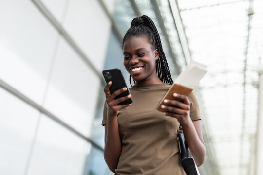 Young african woman use on cellphone and holding passport in airport terminal while waiting for flight