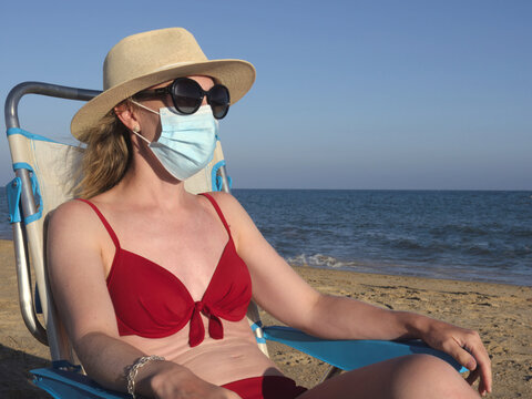 Woman in red bikini, sunglasses and hat wearing surgical face mask at beach. New normality in covid-19 pandemic