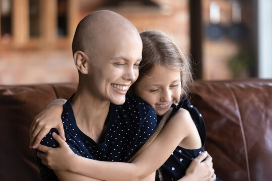 Cute little girl hug cuddle sick cancer patient hairless mom show love and support, happy grateful small daughter embrace caress ill bald young mother, suffer from health problems, healthcare concept