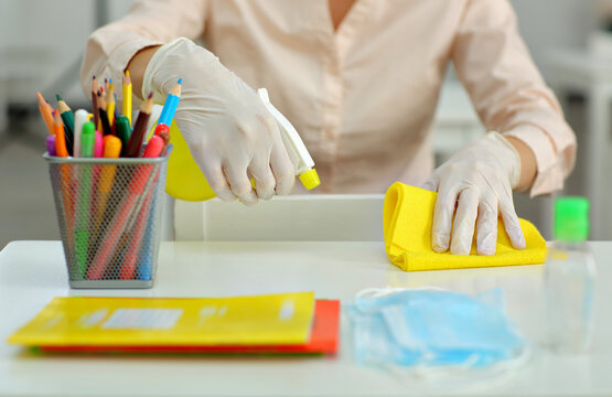 woman in a medical gloves treats and disinfects desk at school before classes
