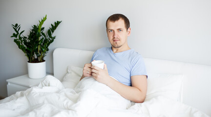good morning concept - handsome man sitting in bed and drinking coffee