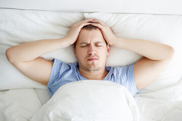 insomnia, depression or headache concept - top view of stressed man lying in bed