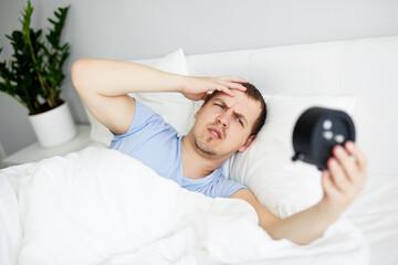 sleepy man waking up early after hearing alarm clock signal