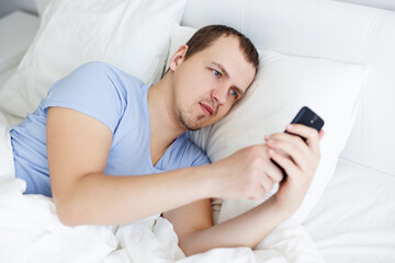 portrait of handsome young man using smartphone lying in bed