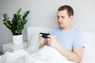 portrait of happy handsome man sitting in bed under blanket and watching video or playing game on smartphone