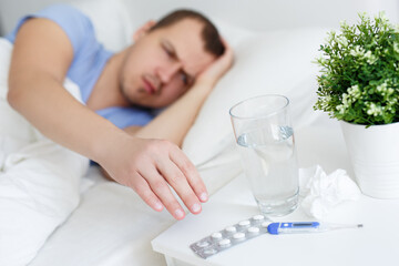 health care and illness concept - sick man with fever taking pills or glass of water from bedside table