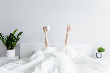 good morning concept - female hands with coffee cup and victory sign sticking out from the blanket at home or hotel
