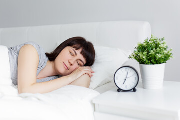 beautiful woman sleeping in bed at home, alarm clock on bedside table