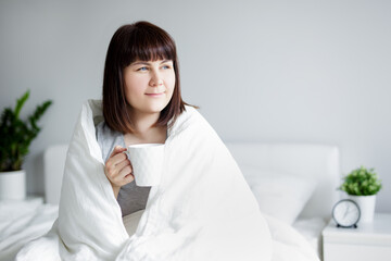 young woman wrapped in blanket sitting in bed, drinking coffee and thinking or dreaming about something at home
