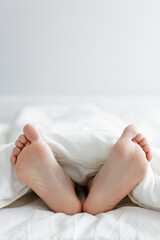 good morning concept - close up of female legs sticking out from the blanket and copy space over white