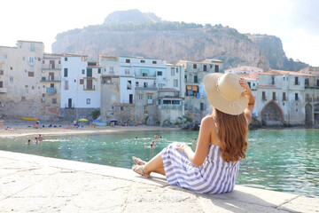 Beautiful young woman with hat sitting looks at stunning panoramic village of Cefalu on Sicily Island, Italy